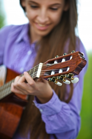 Smiling teenage girl playing guitar, against green of summer park. Stock Photo - 14259522