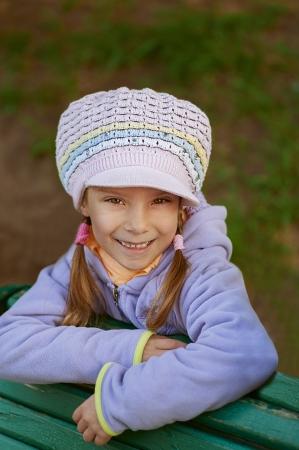 Happy girl-preschooler sitting on green bench in city park. Stock Photo - 14521718