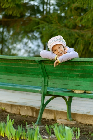 Happy girl-preschooler sitting on green bench in city park. photo