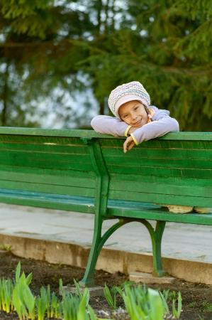 Happy girl-preschooler sitting on green bench in city park. photo
