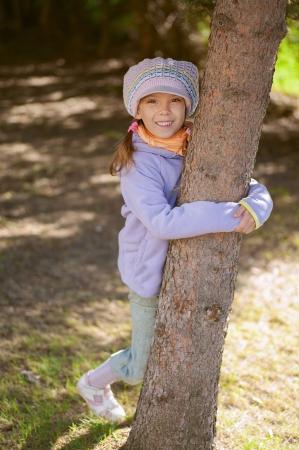Girl-preschooler hands clasped tree in city park. Stock Photo - 14521725