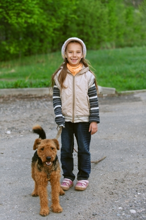Little girl with terrier in city park. photo