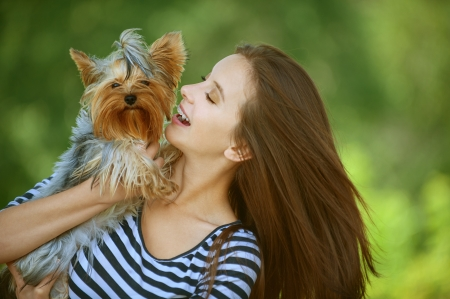 Young beautiful woman with Yorkshire Terrier, against green of summer park. photo