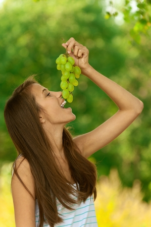viands: Young attractive woman eating grapes, against green of summer park.