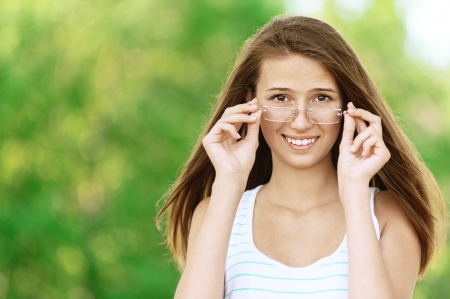 Young attractive woman wears glasses, against green of summer park. photo