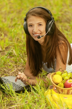 viands: Beautiful young woman with headset lie on grass and working on laptop, against green of summer park. Stock Photo