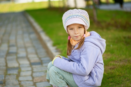 Happy girl-preschooler sitting on stone curb in a city park. Stock Photo - 14521904