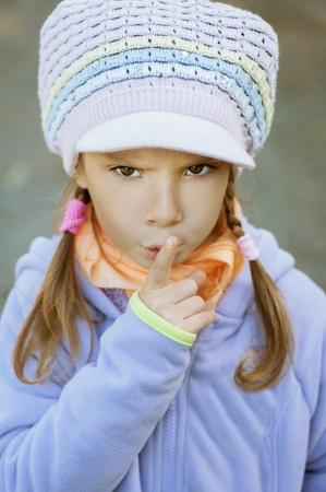 Girl-preschooler in blue jacket, put finger to his lips. photo