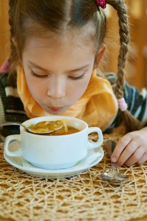 Girl-preschooler eats a tasty meal in cozy restaurant. Stock Photo - 14521905