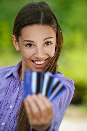 Smiling teenage girl shows credit card, against green of summer park. photo