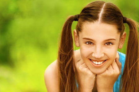 Beautiful smiling teenage girl, against green of summer park. Stock Photo - 14521780