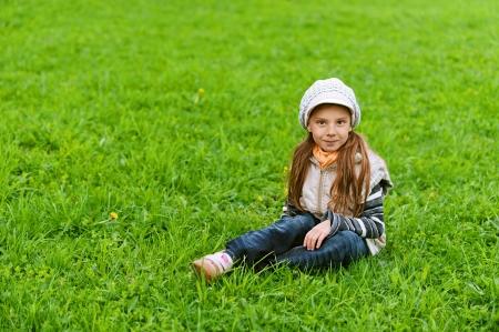 Happy girl-preschooler on green grass in spring city park. Stock Photo - 14521908