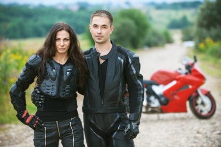 motociclista: Pareja joven en el fondo de la hermosa moto.
