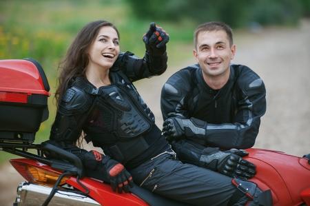 motociclista: Pareja joven en bicicleta hermosa en la carretera. Foto de archivo