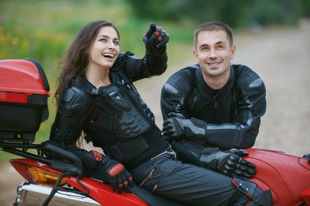 motorcyclist: Young couple on beautiful bike on road.