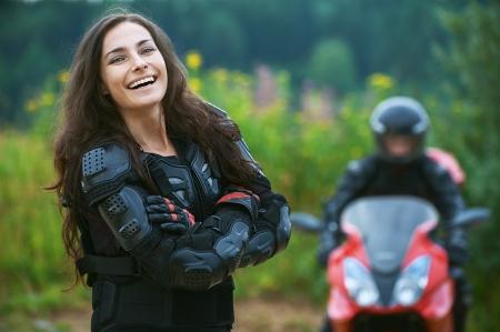 motociclista: Joven mujer motociclista en el fondo de la bici hermosa. Foto de archivo