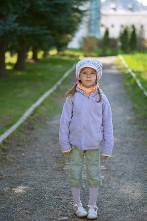 Girl-preschooler in full-length on track in city park.