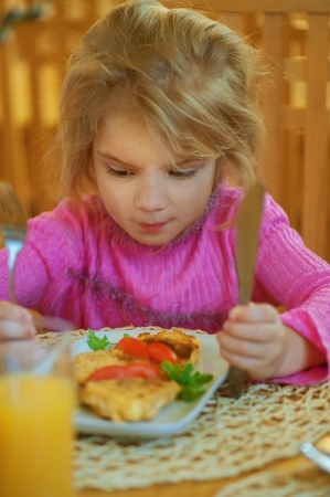 Girl-preschooler eats a tasty meal in cozy restaurant. photo