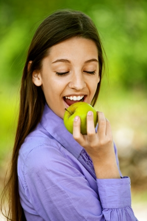 Smiling teenage girl biting an apple, against green of summer park. photo