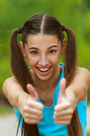 Smiling teenage girl picks up big thumbs up, against green of summer park. Stock Photo - 14720031