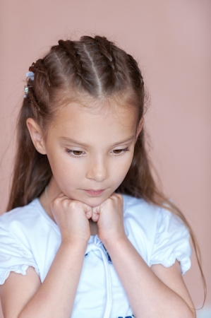 Girl-preschooler thinking, on pink background. photo
