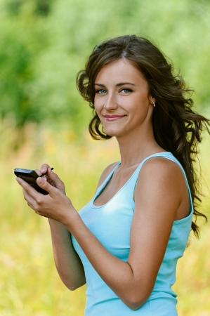 Beautiful young woman close-up in blue shirt is typing with stylus on device, against green of summer park. photo