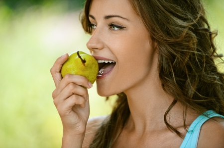 Beautiful young woman close-up in blue shirt pear bites, against green of summer park. Stock Photo - 14720058