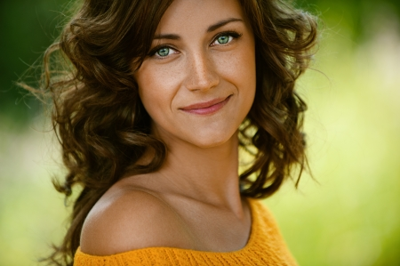 fille pull: Belle jeune femme en gros plan dans le chandail orange, fond vert du parc de l'�t�.