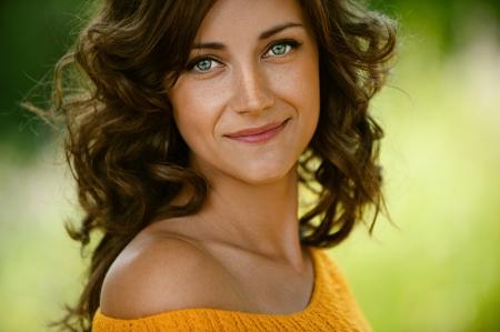 ojos verdes: Joven y bella mujer de cerca en el suéter de color naranja, contra el verde del parque de verano. Foto de archivo