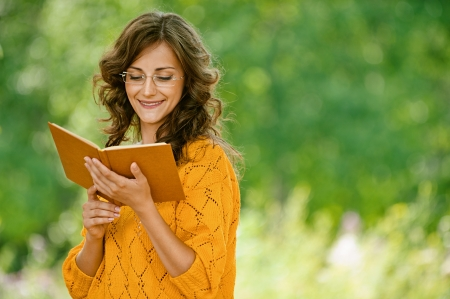 Beautiful young woman close-up in orange sweater reading book, against green of summer park. Stock Photo - 14720065