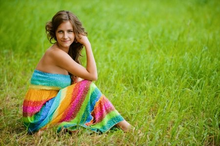 Beautiful young woman in colorful dress sitting on grass, against green of summer park. photo