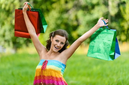 frock: Beautiful young woman in colorful dress happily holds up with shopping bags, against green of summer park.