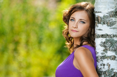 Beautiful young woman in purple dress is based on sad birch, against green of summer park. Stock Photo - 14720051