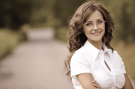 Beautiful young woman in white business suit and glasses smiling, against green of summer park. Stock Photo - 14720040