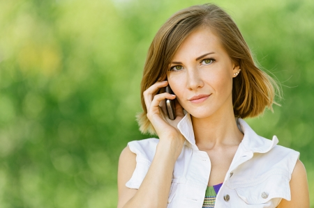 mobile sms: Pretty young woman talking on cell phone close up, against green of summer park.