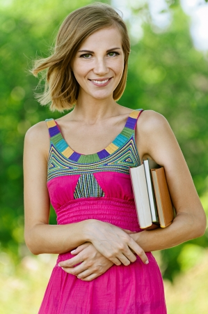 Portrait of smiling beautiful young woman with books, against green of summer park. Stock Photo - 14720039