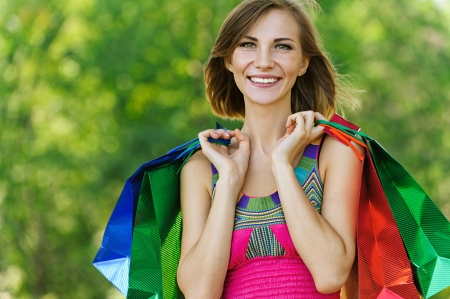Portrait of smiling beautiful young woman with shopping, against green of summer park. Stock Photo - 14720068