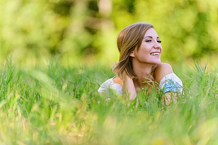 Portrait of beautiful young woman in grass, against green of summer park. Stock Photo - 14720038