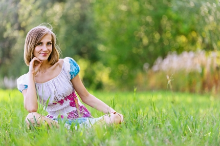 Portrait of smiling beautiful young woman and her little daughter sitting on grass, against green of summer park. photo