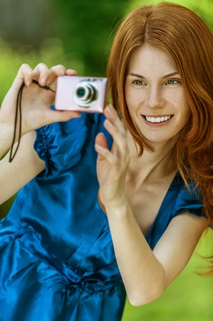 aslant: Portrait of red-haired smiling beautiful young woman in blue blouse with camera, against green of summer park. Stock Photo