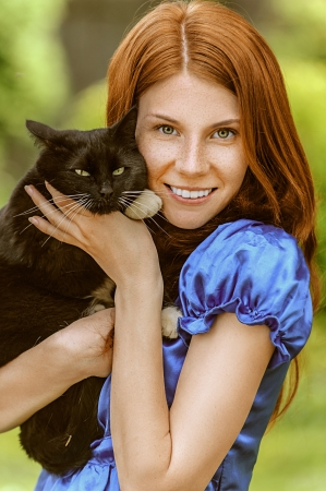 Red-haired smiling beautiful young woman in blue blouse with black cat, against green of summer park. photo