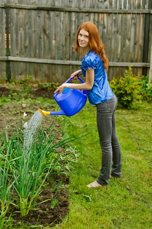Red-haired smiling beautiful young woman in blue blouse bow waters from watering, against green of summer park. photo