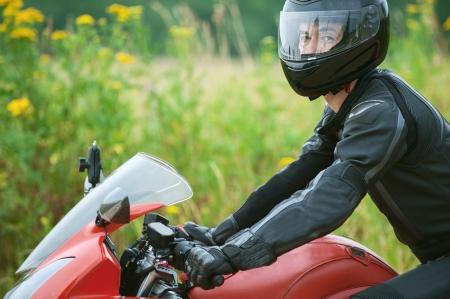 casco moto: Hombre joven que monta bicicleta agradable en el camino.