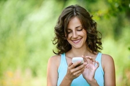 Charmante jonge vrouw close-up in blauw overhemd leest bericht naar mobiele telefoon, tegen groen van de zomer park. Stockfoto