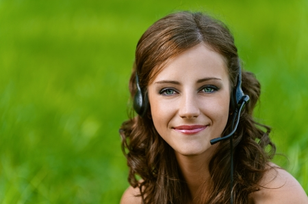 Beautiful young woman close up in headphones and microphone, against green of summer park. Stock Photo
