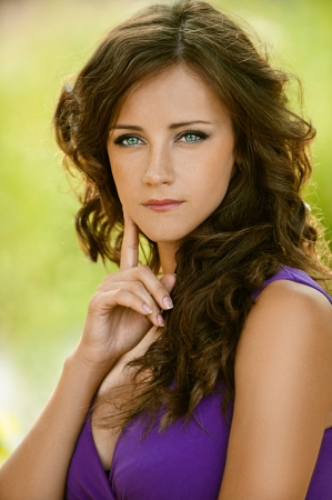 Beautiful young woman in purple dress thought, against green of summer park. photo