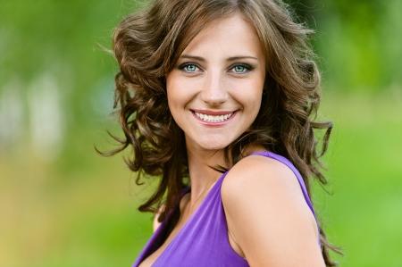 Mooie jonge vrouw in een paarse jurk gelukkig glimlacht, tegen groen van de zomer park.