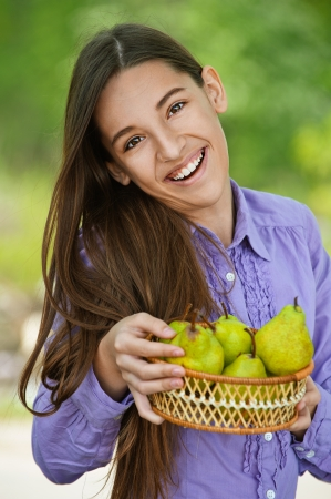 Smiling teenage girl holding basket of pears, against green of summer park. photo