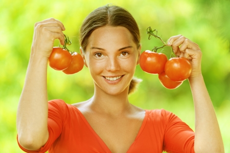 Portrait of dark-haired smiling beautiful young woman in red blouse with tomato, against green of summer park. photo