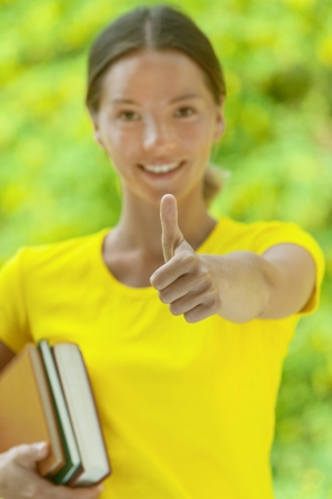 green thumb: Dark-haired smiling beautiful young woman in yellow blouse and with books lifts thumb upwards, against green of summer park.